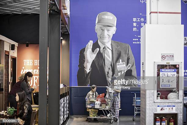 Customers arrange a shopping cart in front of an advertisement featuring the photograph of WalMart Stores Inc founder Sam Walton at the company's...