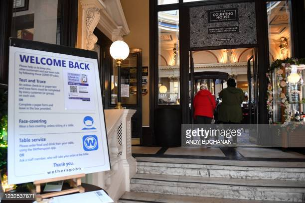 Customers arrive at a re-opened Wetherspoons pub in Glasgow on April 26, 2021 following the relaxing of some Covid-19 restrictions in Scotland, after...