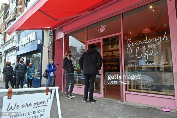 Customers arrive to purchase goods at the Sourdough Sophia bakery in north London on March 18, 2021. - When Britain first entered lockdown in March...