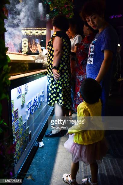 customers at a night market in urumqi - sergio amiti stock pictures, royalty-free photos & images