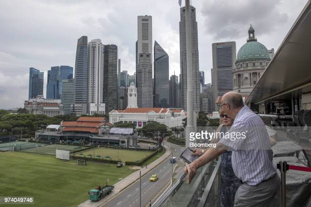Customers at a restaurant look out from the balcony as commercial buildings stand in the central business district of Singapore on Wednesday June 13...