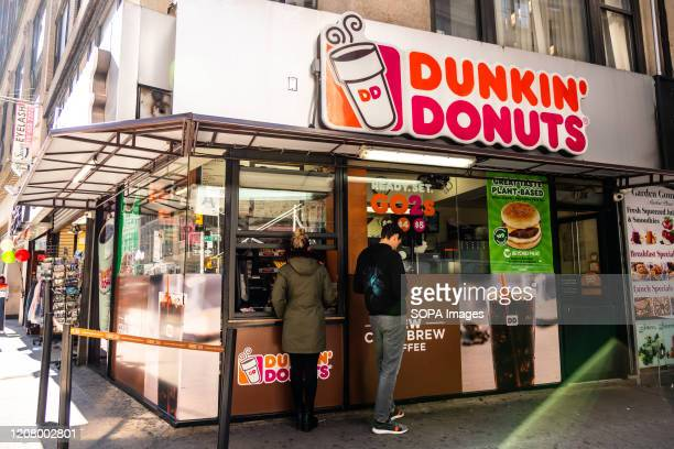 Customers at an American multinational coffeehouse and donut company Dunkin' Donuts store in New York City