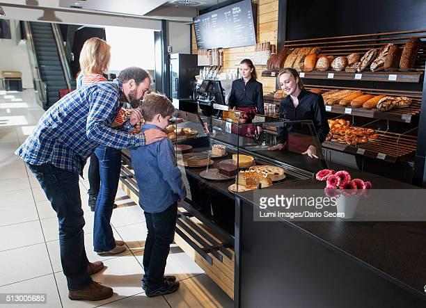 Customers at bakery counter choosing organic cake