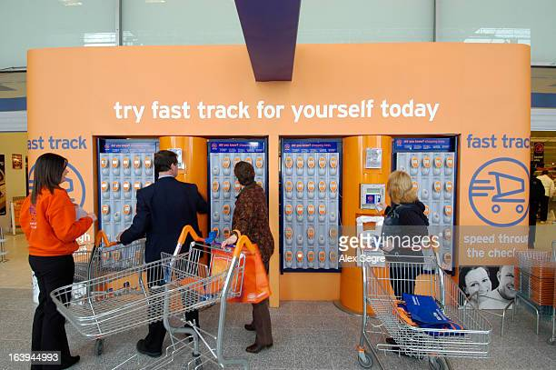 CONTENT] Customers at rack of self scanning devices at Sainsbury's supermarket England UK
