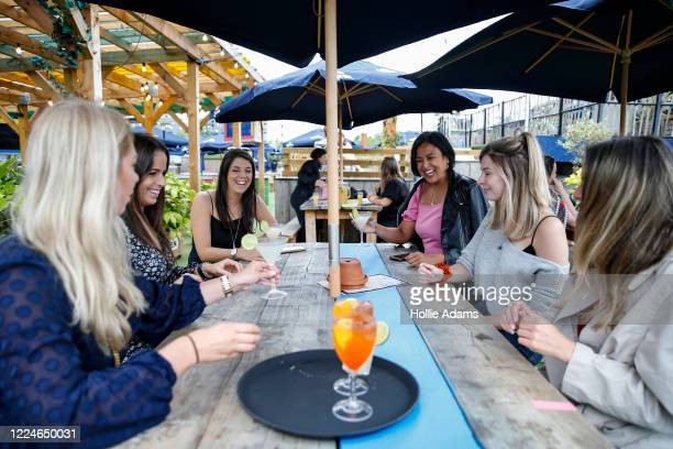 Customers at Skylight Rooftop bar enjoy a drink together on July 4, 2020 in London, United Kingdom. The UK Government announced that Pubs, Hotels and...