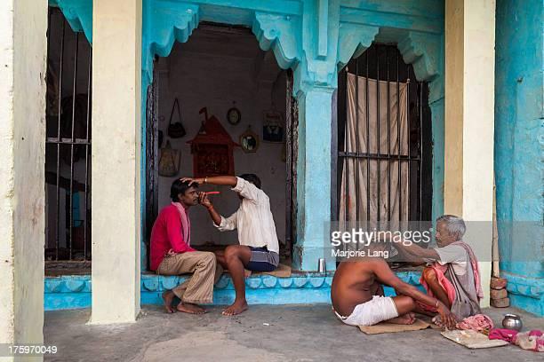 Customers being shaved in a street barbershop near the ghats by the Ganges river in Gaudoliya, old Varanasi, Uttar Pradesh, India.