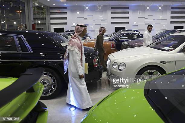 Customers browse a collection of luxury automobiles including a Rolls Royce Bentley BMW and Lamborghini on display at the Saden Al Araba Group car...