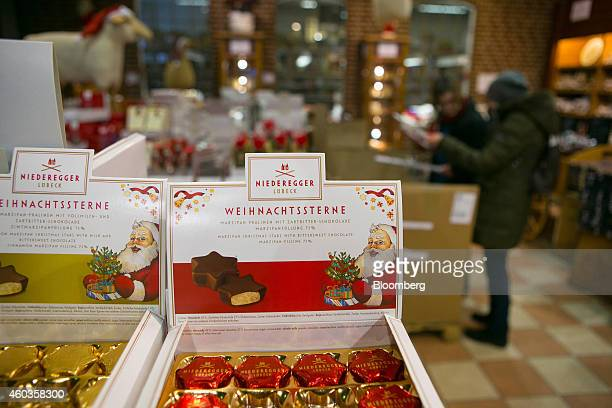 Customers browse a festive Christmas confectionary display in the gift shop at the JG Niederegger GmbH marzipan factory in Luebeck Germany on Tuesday...