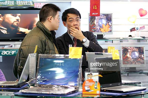 Customers browse Acer Inc laptop computers in an electronics store in Taipei Taiwan Tuesday March 28 2006