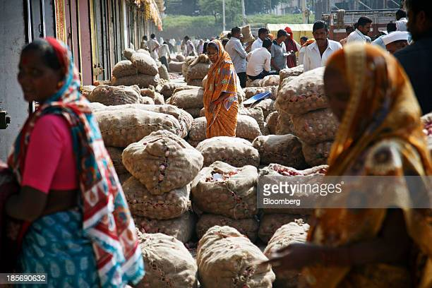 Customers browse bags of onions displayed for sale at a wholesale market in Nashik Maharashtra India on Wednesday Oct 23 2013 Onion prices in India...