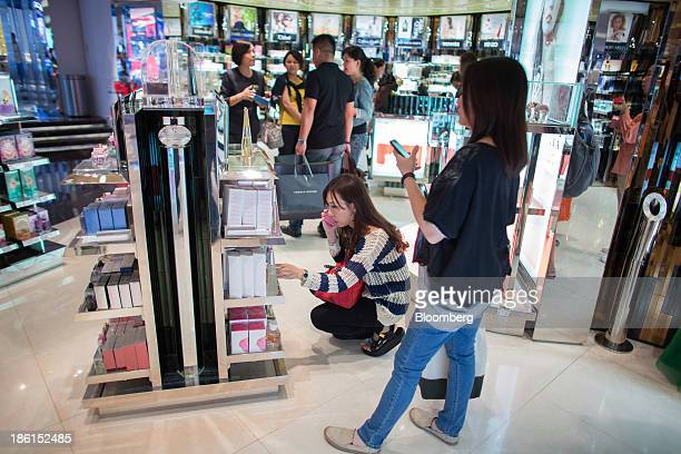 Customers browse bottles of perfume while using mobile devices inside the DFS Group Ltd T Galleria store in the shopping district of Tsim Sha Tsui in...
