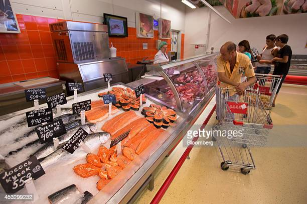 Customers browse counters filled with meat and imported Norwegian salmon inside an OAO Magnit hypermarket in Krasnodar Russia on Thursday Aug 7 2014...