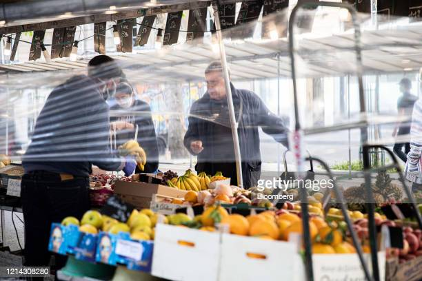Customers browse fresh produce behind protective cellophane screens on a fruit and vegetable stall at Marche SaxeBreteuil in Paris France on Thursday...
