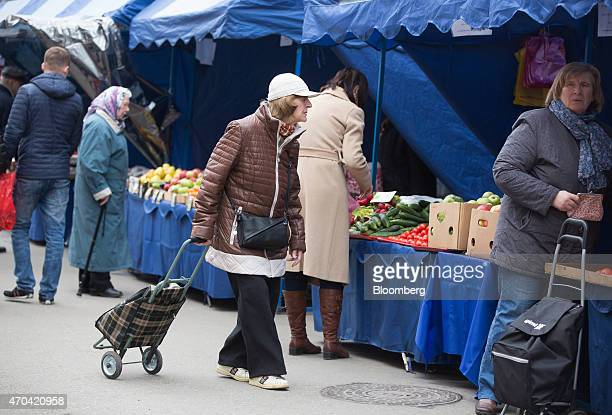 Customers browse fruit and vegetable stalls at an open air street market in Moscow Russia on Saturday April 18 2015 Russia will extend a freeze on...