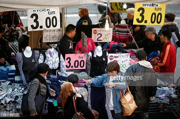 Customers browse goods on clothing stalls displayed with large Euro price signs at a market in Rome Italy on Wednesday Nov 2 2011 Italian Prime...