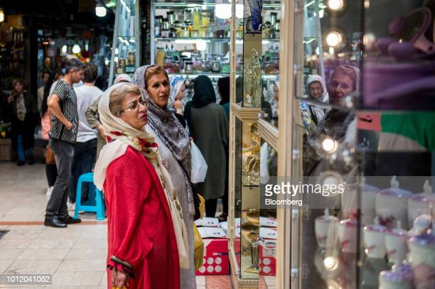 Customers browse goods on display in a store window inside the Grand Bazaar in Tehran Iran on Monday Aug 6 2018 Irans central bank acting on the eve...