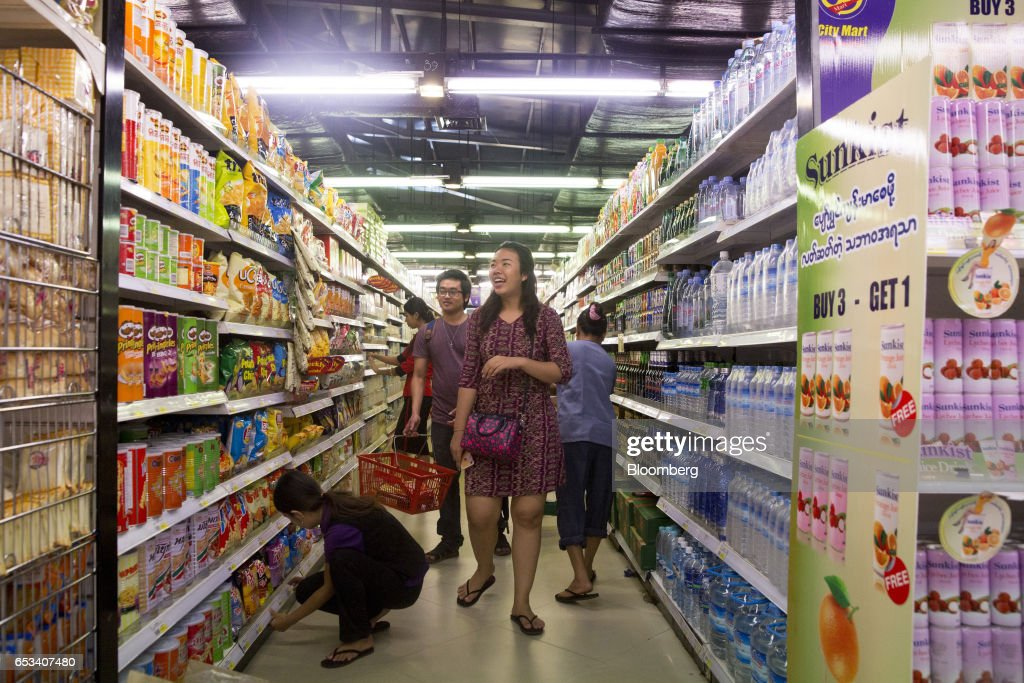 Customers browse groceries displayed in the aisle of a City Mart Supermarket store, operated by City Mart Holdings Co., in Yangon, Myanmar, on Saturday, March 11, 2017. City Mart has 20 years of market knowledge to help it compete against international players, said Win Win Tint, managing director of City Mart in a Bloomberg interview on March 9. Photographer: Brent Lewin/Bloomberg via Getty Images
