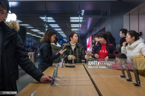 Customers browse inside an Apple Inc store in on January 3 2019 in Shenzhen China Apple Inc lowered its revenue guidance on Wednesday blaming China's...