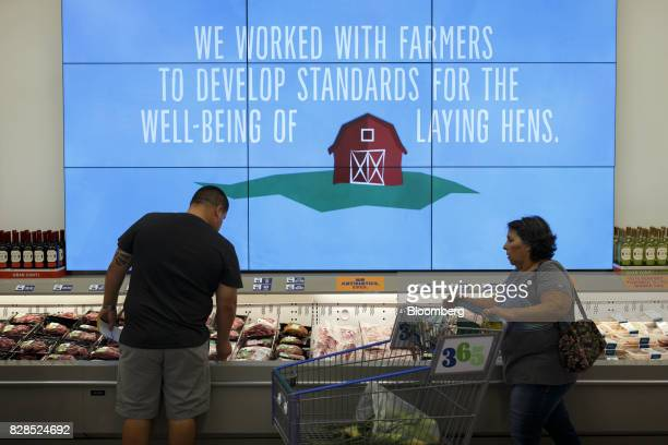 Customers browse meat and seafood displayed for sale during the grand opening of a Whole Foods Market 365 location in Santa Monica California US on...