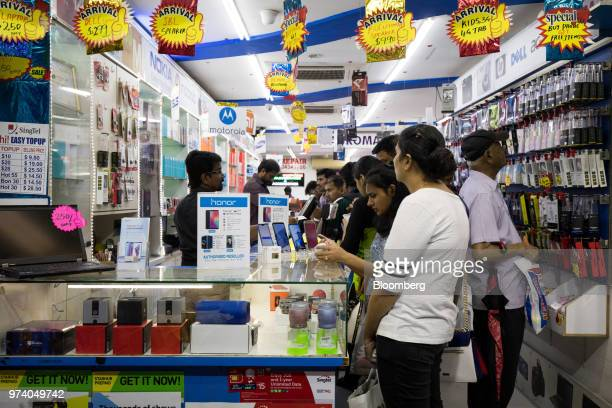 Customers browse mobile phones at a store in the Little India area of Singapore on Wednesday June 13 2018 Tourism as well as the consumer sector will...