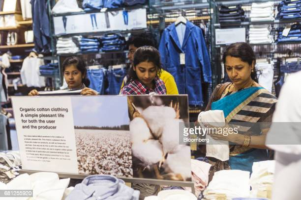 Customers browse organic cotton clothing at a Muji store operated by Ryohin Keikaku Co in a joint venture with Reliance Brands Ltd in New Delhi India...