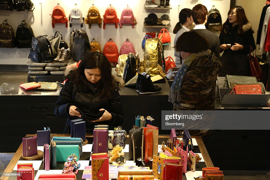 Customers browse purses and bags inside an MCM Holdings AG store on Garosugil street in the Gangnam district of Seoul, South Korea, on Sunday, Dec. 22, 2013. Consumer prices climbed 0.9 percent in November from a year earlier after a 0.7 percent increase in October that was the smallest gain since July 1999. Photographer: SeongJoon Cho/Bloomberg via Getty Images