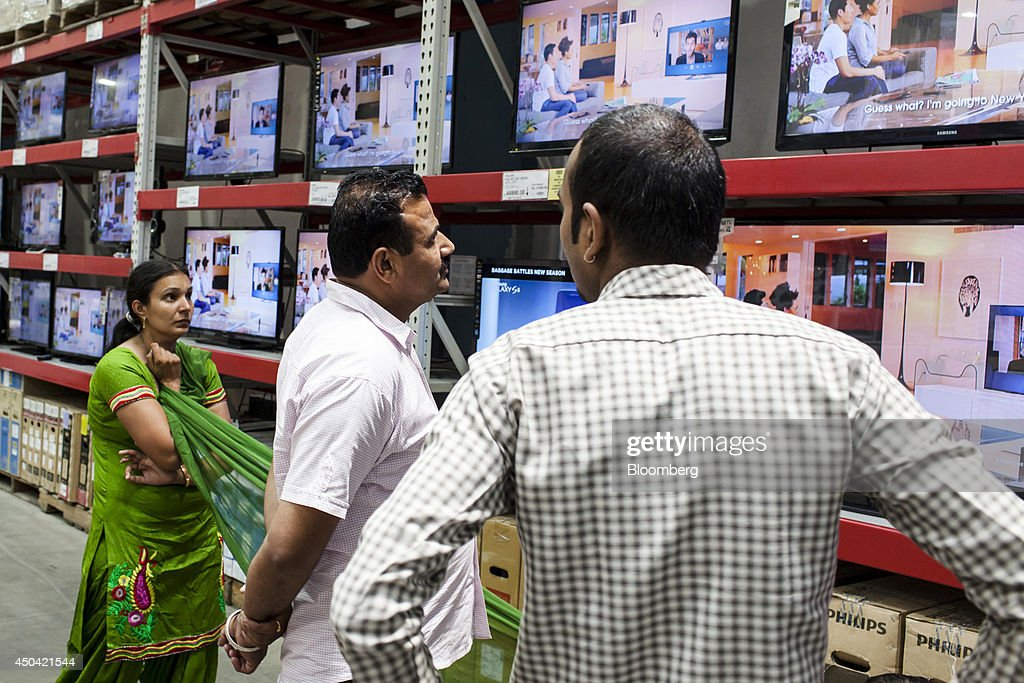 Customers browse Samsung Electronics Co flat screen televisions on display at a Walmart India Pvt Best Price Modern Wholesale store in the town of...