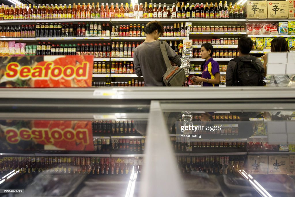 Customers browse sauces displayed on shelves inside a City Mart Supermarket store, operated by City Mart Holdings Co., in Yangon, Myanmar, on Saturday, March 11, 2017. City Mart has 20 years of market knowledge to help it compete against international players, said Win Win Tint, managing director of City Mart in a Bloomberg interview on March 9. Photographer: Brent Lewin/Bloomberg via Getty Images