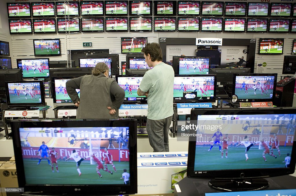 Customers browse televisions whilst the football World Cup is shown at a Currys store in London, U.K., on Friday, June 18, 2010. U.K. retail sales increased more than economists forecast in May as shoppers bought electrical goods such as wide-screen televisions to watch the World Cup soccer tournament. Photographer: Chris Ratcliffe/Bloomberg via Getty Images