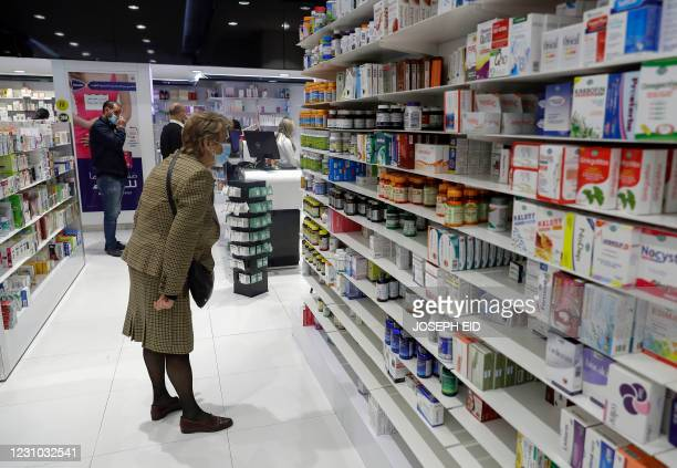 Customers browse the aisles for medicine at a pharmacy in the Lebanese capital Beirut, on February 2, 2021. - With the economy in a tailspin and the...