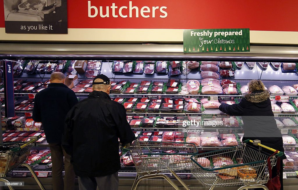 Customers browse the chilled meat section inside a Morrisons supermarket, operated by William Morrsons Supermarkets Plc, in Chadderton, U.K., on Monday, Dec. 17, 2012. The British Christmas is the biggest epicurean occasion of the year, with households spending a total of 4 billion pounds on food in the final week before Dec. 25. Photographer: Paul Thomas/Bloomberg via Getty Images