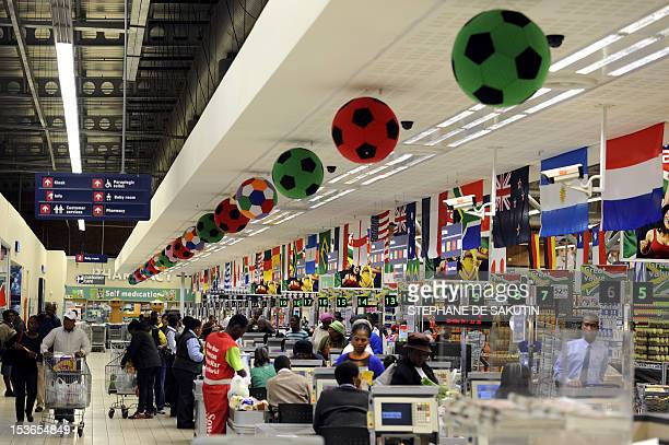Customers buy and pay their goods at cashiers decorated with footballs and flags for the upcoming Football World Cup 2010 on May 21 2010 in a...