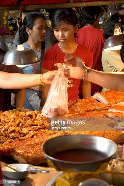 Customers buy bags of barbecued pork at a stall at the Chatuchak Weekend Market on the outskirts of Bangkok