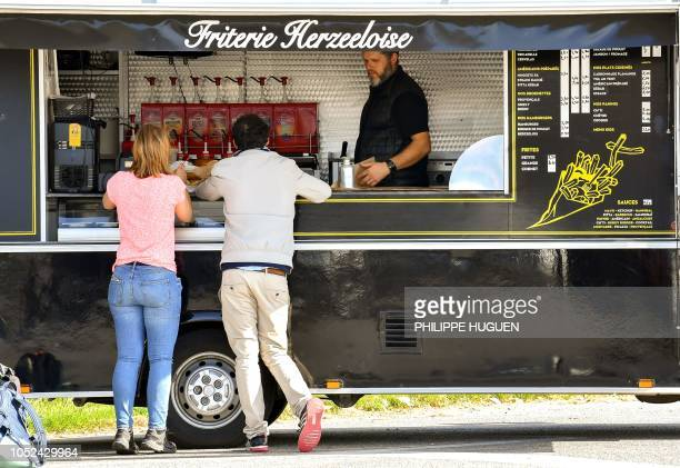 Customers buy French fries at a food truck in Steenvoorde northern France on October 15 2018 as the harvest of potatoes reduced following summer...
