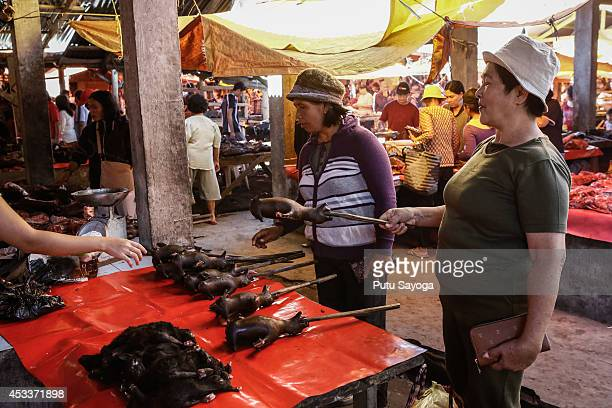 Customers buy roasted bat at Langowan traditional market on August 9 2014 in Langowan North Sulawesi The Langowan traditional market is famous for...