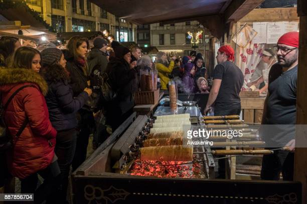 Customers buy the traditional Hungarian Chimney Cake at Vorosmarty Square Christmas market on December 7 2017 in Budapest Hungary The traditional...