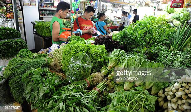 Customers buy vegetables at a farmers market in Quezon City suburban Manila on September 5 2012 Inflation surged to a sevenmonth high of 38 percent...