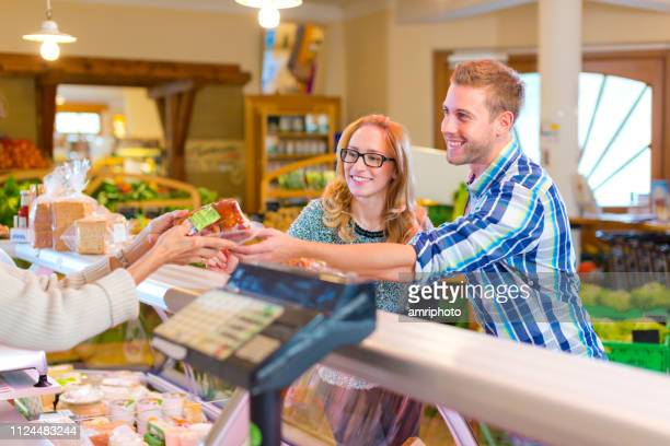 customers buying food on meat counter of small supermarket - health food shop stock pictures, royalty-free photos & images