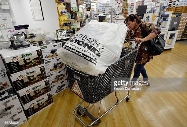 Customers carry bags from Bed Bath & Beyond store on April 10, 2013 in Los Angeles, California. The home goods retailer is expected to release...