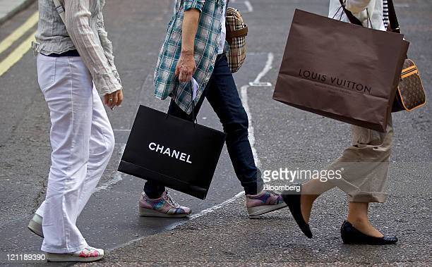 Customers carry Chanel SA and LVMH Moet Hennessy Louis Vuitton SA-branded shopping bags across Old Bond Street in central London, U.K., on Monday,...
