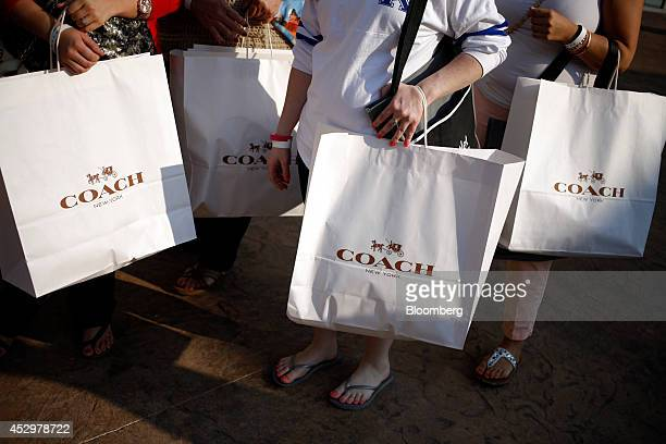 b7d641f36fbf64 Customers carry Coach Inc shopping bags after shopping at a store during a  charity preview event