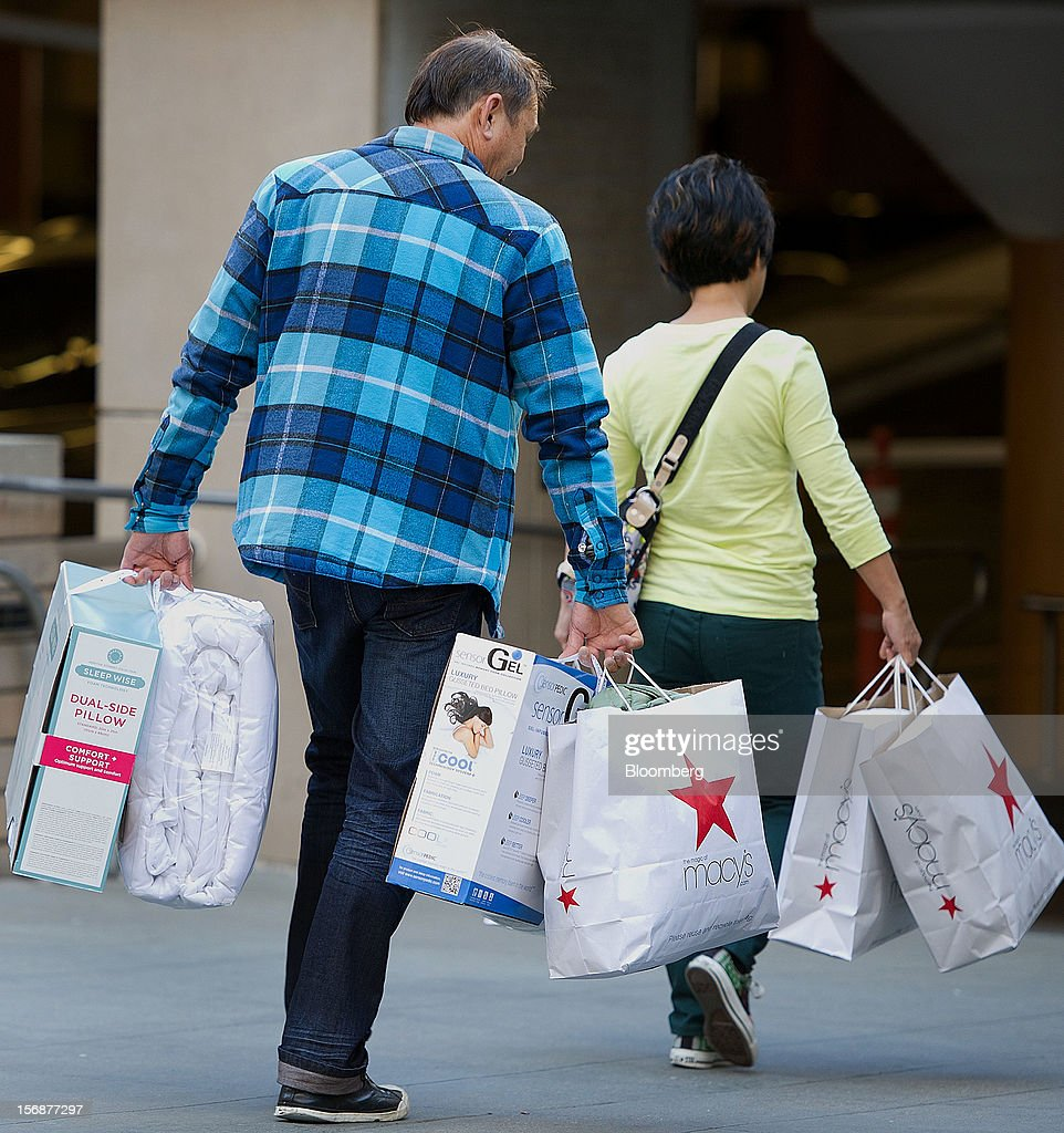Customers carry Macy's Inc. shopping bags in San Francisco, California, U.S., on Friday, Nov. 23, 2012. To get shoppers to spend more than last year, retailers have continued to turn Black Friday, originally a one-day event after Thanksgiving, into a week's worth of deals and discounts. Photographer: David Paul Morris/Bloomberg via Getty Images