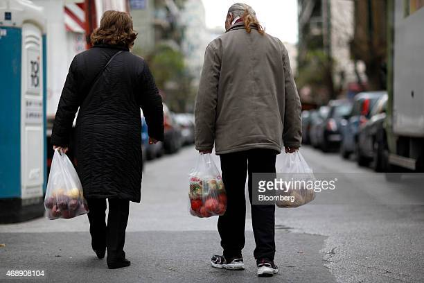 Customers carry plastic bags filled with fresh vegetable bought from a street market in Athens Greece on Wednesday April 8 2015 Russian President...