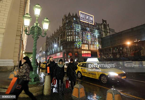 Customers carry shopping bags along the street past a yellow taxi cab after visiting the TsUM luxury department store center also known as the...