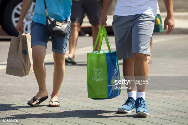 Customers carry shopping bags during the grand opening of a Whole Foods Market 365 location in Santa Monica California US on Wednesday Aug 9 2017 The...
