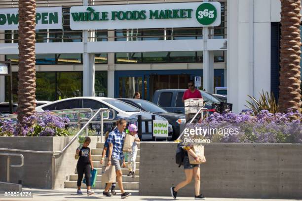 Customers carry shopping bags outside of a Whole Foods Market 365 location during the grand opening in Santa Monica California US on Wednesday Aug 9...