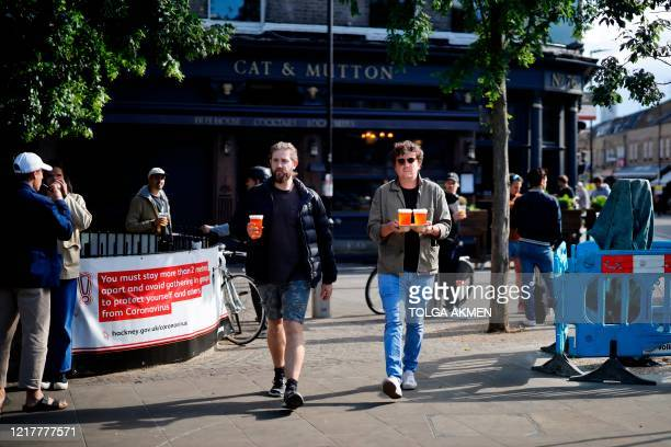 Customers carry their takeaway draught beer in plastic cups from a pub in Broadway Market, London on June 5 as lockdown measures are eased during the...