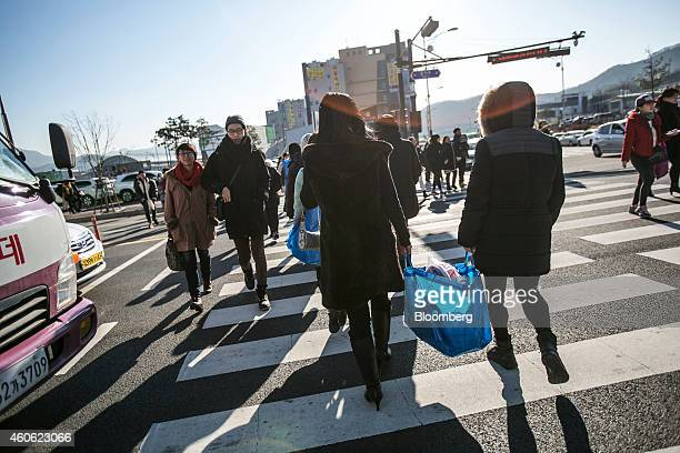 Customers carrying Ikea AB shopping bags cross a road in Gwangmyeong Gyeonggi province South Korea on Thursday Dec 18 2014 Ikea the world's largest...