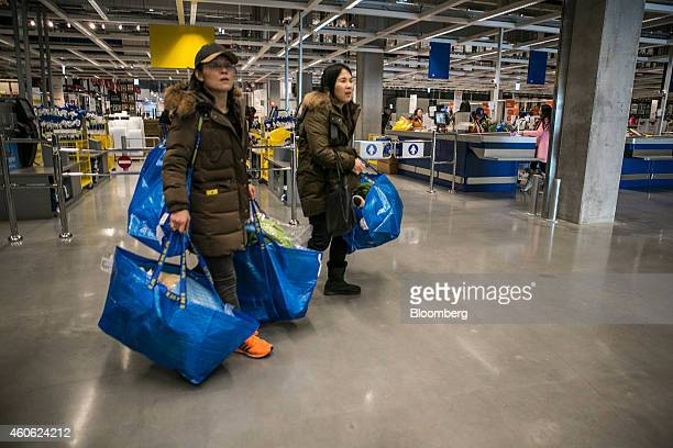 Customers carrying Ikea AB shopping bags leave the company's store in Gwangmyeong Gyeonggi province South Korea on Thursday Dec 18 2014 Ikea the...