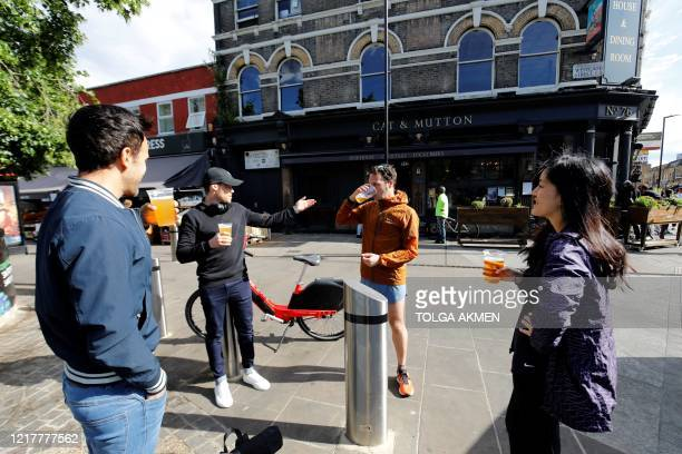 Customers chat as they drink their takeaway draught beer in plastic cups outside a pub in Broadway Market, London on June 5 as lockdown measures are...